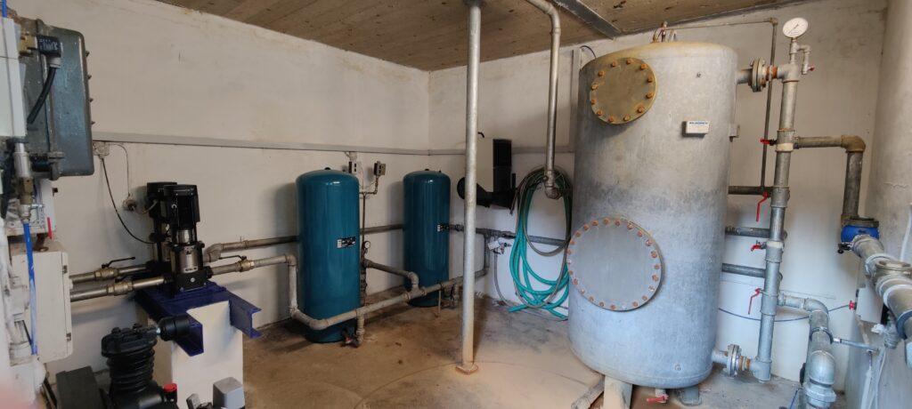 Inde i vandværket kan man se fra venstre: Elskab, to pumper, 2 tryk tanke, filtertank og vanduret.